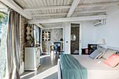 Elegant bedroom in Mediterranean style with stone walls
