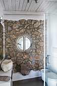 Round window in stone wall of small bathroom