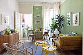 Yellow sofa and side tables in bright interior with green walls