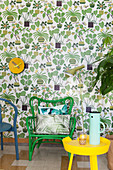 Green chair and yellow side table in reading area against wallpaper with plant motifs