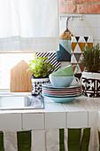 Geschirr und Kräutertöpfe auf weiß gefliester Küchenablage