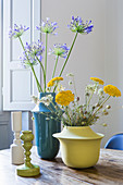 Ensemble von verschiedenen Blumenvasen und Kerzenständern als Tischdeko