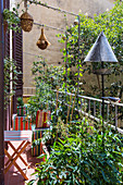 Striped folding furniture, plants, nesting boxes and bird feeder on urban balcony