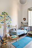 Kinderzimmer in Altbauwohnung mit nostalgischem Metallbett und gemaltem Baummotiv