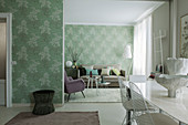 View from dining area into lounge with green wallpaper and pastel furniture