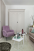 Small table, purple armchair and white wooden cupboard in living room