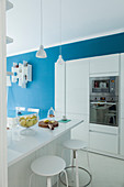 White kitchen cabinets with fitted appliances, counter with bar stools and blue wall
