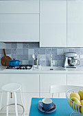 White fitted kitchen with tiled splashback