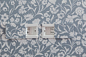 Plug sockets with sliding covers in wall with patterned wallpaper