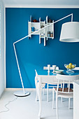 Table, chairs, standard lamp and wall-mounted shelving unit in blue and white dining area