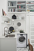 Washing machine in small kitchen below shelves in studio apartment