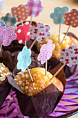 Muffins decorated with handmade paper flowers on toothpicks