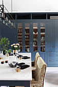Blue cabinets with glass doors and set table in kitchen-dining room