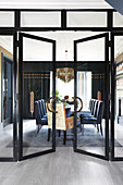 Open double doors in glass wall leading into elegant dining room
