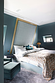 Bed with high, upholstered headboard on sloping wall in elegant bedroom