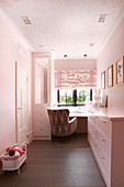 Desk and fitted cupboards in girl's bedroom decorated entirely in pink