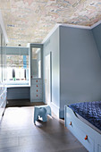 Boy's room decorated entirely in pale blue with vintage-effect wallpaper on ceiling