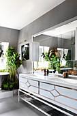 Twin sinks and numerous houseplants in glamorous bathroom