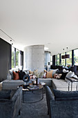 Sofa and armchairs in luxurious open-plan interior in shades of grey