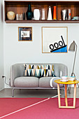 Collection of vases on retro wooden shelf above grey two-seater sofa