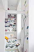 Doorway leading into children's sleeping area with desk and tall shelving