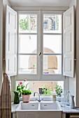 Spüle vor Sprossenfenster mit weißen Innen-Fensterläden
