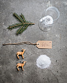 Wine glass, pine twig, name tag, deer figurines and salt for making a winter-landscape place card
