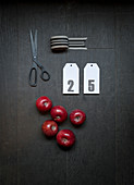 Ribbon, numbered card, red apples and scissors on dark surface