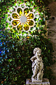 Cherub playing flute below illuminated wreath on wall in garden