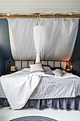 Grey and white double bed with ruffles and DIY canopy under sloping ceiling