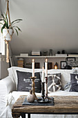Sofa and arrangement of candles on rustic wooden coffee table in cosy seating area