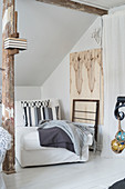 White chaise chair below sloping ceiling with wooden beams