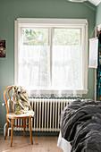 Bistro chair below window with net curtains in bedroom
