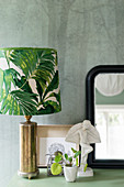 Table lamp with leaf motif, Chinese money plant and small sculpture in front of mirror