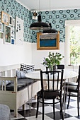 Table with black chairs and kitchen bench on chequered floor