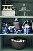 Crockery with blue floral pattern and bowl of candles in cupboard