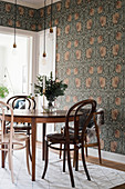 Bistro chairs at round table in dining room with Arts and Crafts wallpaper