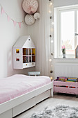 Dolls' house hung on wall in play area next to bed in girl's bedroom
