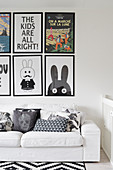 Scatter cushions on white sofa below gallery of comic art