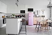 Großzügiger Küchenbereich in Weiß und Grau mit Kücheninsel und Esstisch