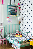 Turquoise metal bed in child's bedroom with horse-patterned wallpaper