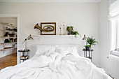 Old brass instrument in frame on wall above rumpled bed