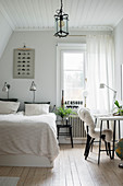Bed and desk in classic guest bedroom decorated in white