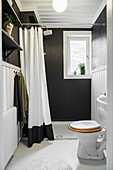 Small shower bathroom with black walls and white floor