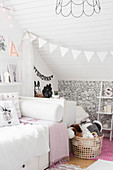 Bed in girl's bedroom with sloping ceiling and patterned wallpaper on knee wall