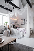 Bed with canopy in white attic room with exposed black roof beams