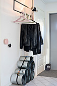 Shoe rack made from pipes bound with lashing strap below coat rack