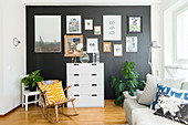 Rocking chair and chest of drawers below gallery of pictures on black wall