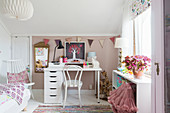 Bistro chair at desk against pink wall in child's bedroom
