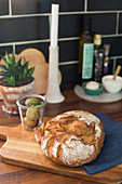 Bread and figs in glass on chopping board in kitchen